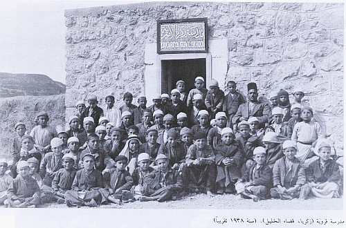 Zakariyya school-children, before they were ethnically cleansed from their city in 1948 by Israeli Defence Forces. Tel Zakariyya, under which lies Azekah, can be seen on the left  in the background.